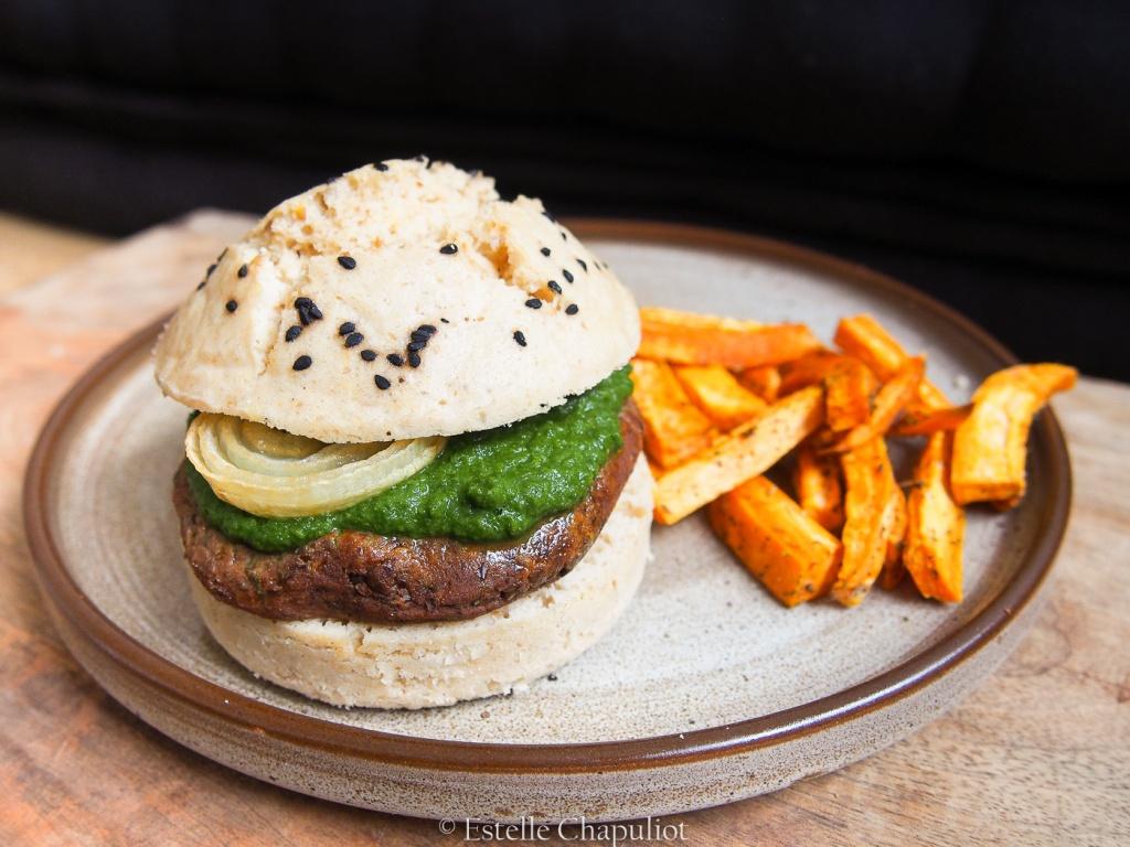 Burger végétal : pain vapeur sans gluten, steak de lentilles beluga, frites de patate douce au four aux herbes, sauce verte, oignons