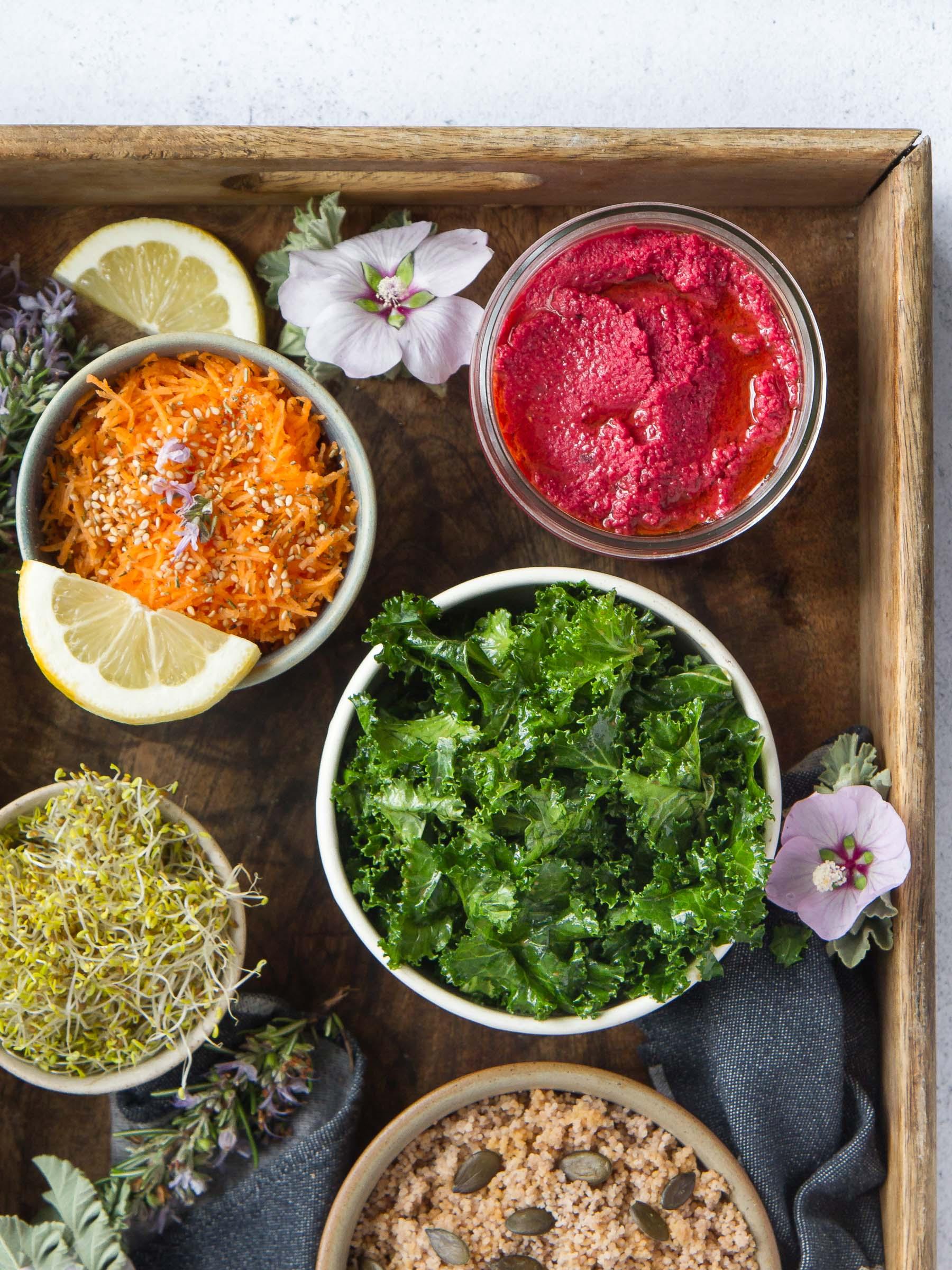 Houmous de fèves à la betterave, salade de chou kale, couscous de sarrasin, alfalfa germé, carottes râpées au thym et citron