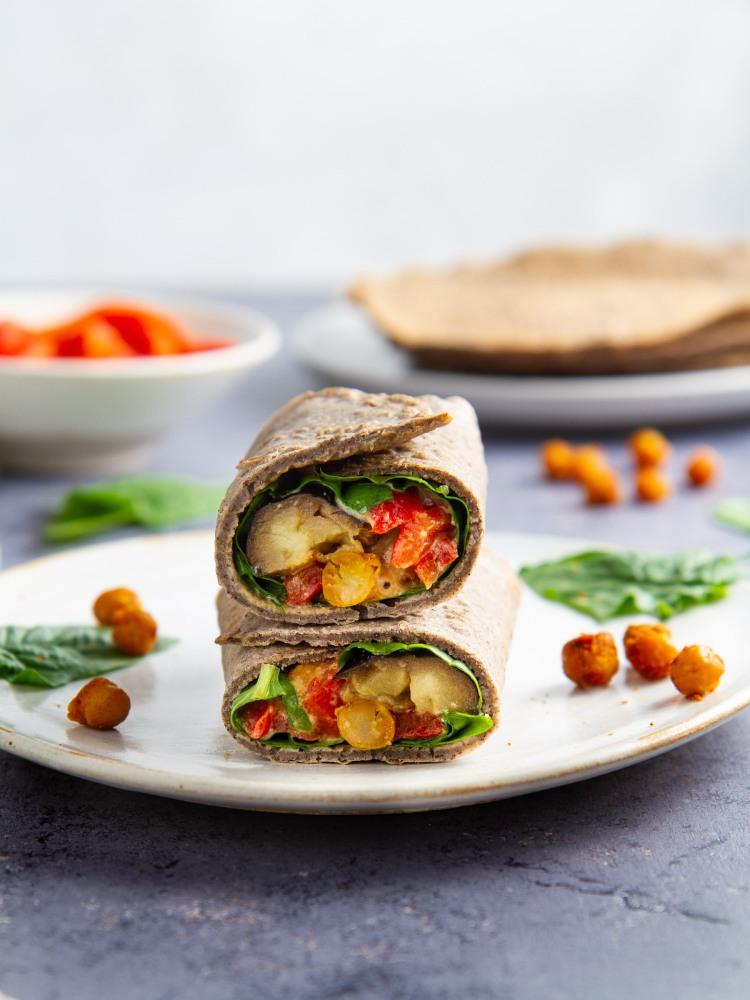 Galettes de sarrasin garnies aux pois chiches et aubergines rôtis, poivronnade, pousses d'épinards et sauce tahin-miso (vegan, sans gluten)